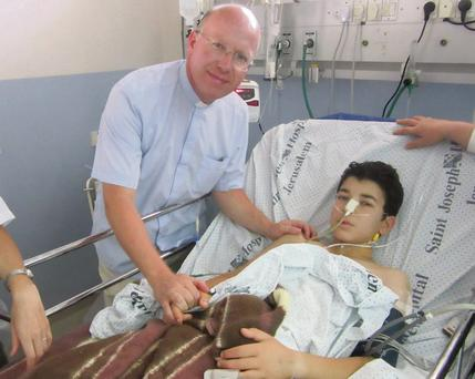 Fr. Billy Swan with a young patient in the hospital in Jerusalem