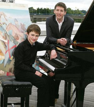 Young pianist Kevin Jenssen on the boardwalk in New Ross last Wednesday and looking on was pianist Finghin Collins at the launch of the New Ross Piano Festival