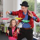 Paul Wheel of the Wobbly Circus helping Romy Belton balance spinning plates in New Ross Library.