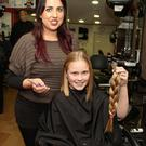 Hair stylist Laura Daly with Casey Doyle from Rathangan who had her hair cut in Anna Furlong's Hair Salon last week and donated it to the Rapunzel Foundation