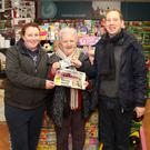 David Looby of the New Ross Standard presenting Anne Moore from Robinstown with €20 at the Village Forecourt in Clonroche with Charlene Travers of the Village Forecourt