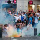 A tear gas grenade explodes near an England fan ahead of England's EURO 2016 match in Marseille