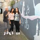 Maria Prochukhan with her mother Tatiana and sister Nadezda (Nadia) at the colourful mural she painted in New Ross