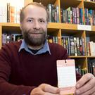 Book shop owner Conor Dervan with the birth tag.