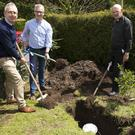 Padraig Cronin, principal; Michael Ryan, chairperson, board of management and Fr Eddie Aughney burying the time capsule