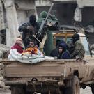 Rebel fighters ride on a pick-up truck in the northern Syrian rebel-held town of al-Rai, Syria