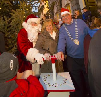 Santa Claus, Mary Browne and Cathaoirleach Willie Fitzharris turning on the Christmas lights
