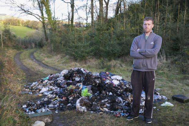 Diarmuid Murphy next to illegal rubbish dumped at Ballyleigh near Ballywilliam