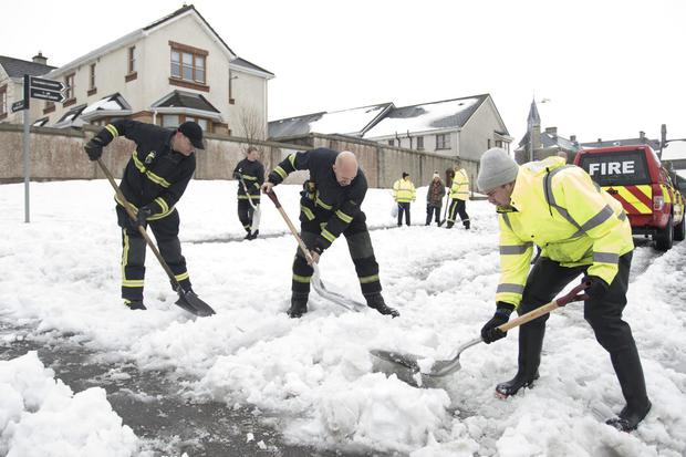 New Ross firemen helping clear snow from the Convent Court housing estate in New Ross after Storm Emma