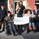 At the presentation of €1,000 to the Irish Wheelchair Association at Porter's Bar, from left (front), Eoin Murphy and Sarah Louise Fortune; (back), Sean Furlong IWA, Stephen Furlong, Service Support Officer, Selina Power, proprietors, Simon and Orla Besanson with their daughter, Grace, John Sugrue and Ger Jordan