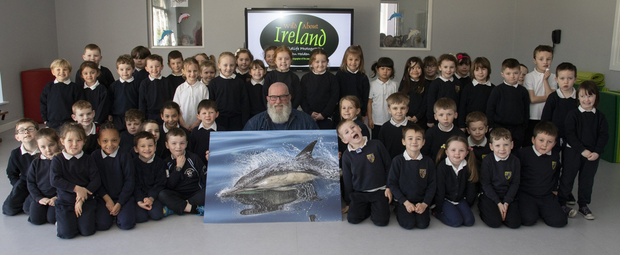 Wildlife photographer John Holden presents a copy of his award-winning photograph to Kilrane National School