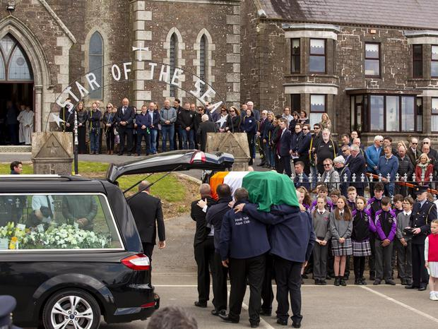 The coffin, draped in the tricolour, is carried into Our Lady, Star of the Sea Church in Duncannon