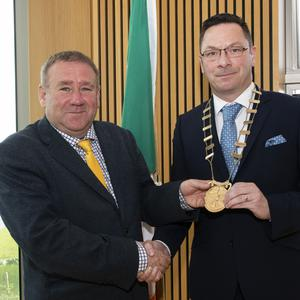Keith Doyle, the outgoing Wexford County Council cathaoirleach, hands over the chains of office to new chairman, Cllr Michael Sheehan