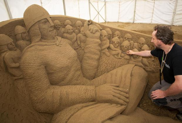 Daniel Doyle from Dublin putting the finishing touches to his sand sculpure themed The Norman Way. Photo: Mary Browne