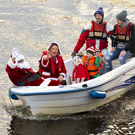Santa Claus, Mrs Claus and Elf arriving into Rosbercon by boat