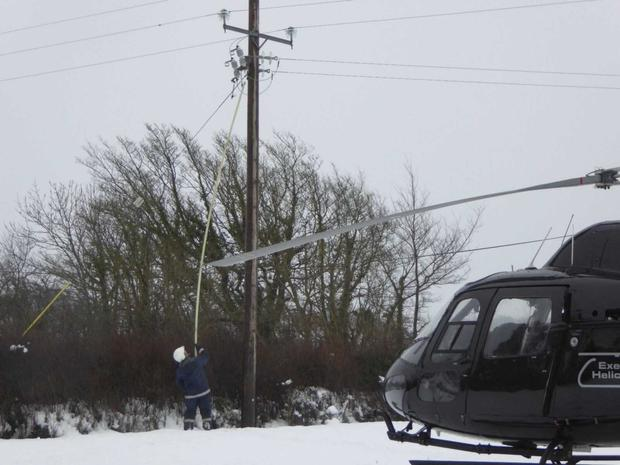 An ESB Networks crew member working in Curracloe beside the helicopter which transported him to the area