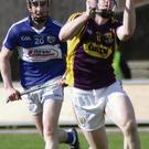 Shane Tomkins gets to the ball ahead of Paddy Purcell of Laois.