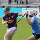 Wexford full-forward Jack Cullen grabs the ball and puts pressure on Dublin's Ben McHugh.