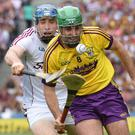 Wexford sweeper Shaun Murphy racing out of defence with Galway's man of the match Conor Cooney in hot pursuit