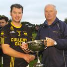 Colm Boland is presented with the cup by Denis Nolan