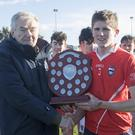 Pat Henderson presenting the shield to Andrew Walsh.