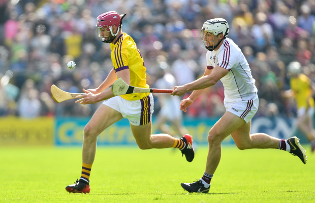 Wexford defender Pádraig Foley on the move with Daithí Burke of Galway giving chase