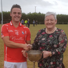 Graham O'Grady gets the cup from Caroline Foxe