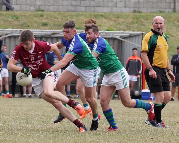 Brendan Halpin of Castletown tries to get away from Glynn-Barntown duo Rioghan Crosbie and Barry Doyle