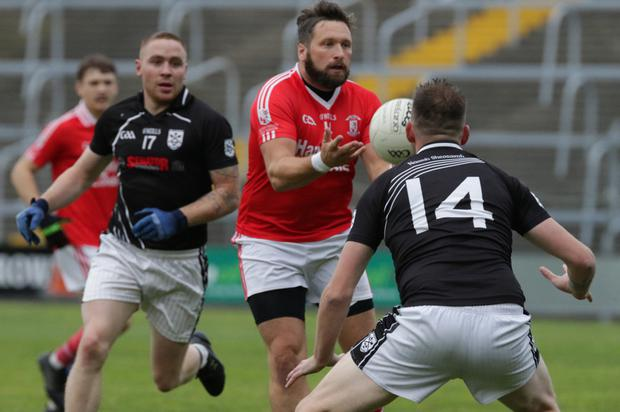 Donal O'Leary of St Mary's (Maudlintown) spots a gap between Eddie Byrne and Andy Moore