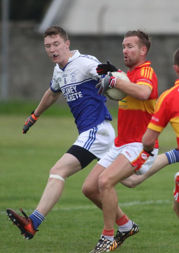 Horeswood captain P.J.Banville has his space closed down by Conor Byrne of Ballyhogue