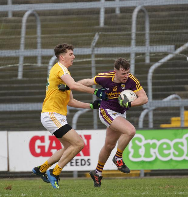 Wexford full-back Mark O'Neill forcefully brushing aside the challenge of Antrim's Rúairí McCann during Sunday's victory