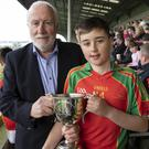Kevin Waters (Chairman) presenting the cup to Jack Canavan, the St. Aidan's captain.
