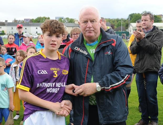 Joe O'Brien, the St. James' captain, receiving his runners-up medal from John Purcell, Chairman of the Cork Féile organising committee. Photograph: George Hatchell