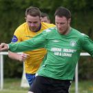 Gary Byrne of North End United closes in on Michael Kinsella of Courtown Hibs
