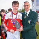 Liam Evans of Moyne Rangers receives the man of the match award from Mick Larkin of the Wexford Football League