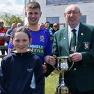 Danny Kearney of the Wexford League presents the Gwyn Jones Cup to Mikey Keane of St. Joseph's, with Gwyn's son, David Jones, and his grand-daughter, Sinéad Jones