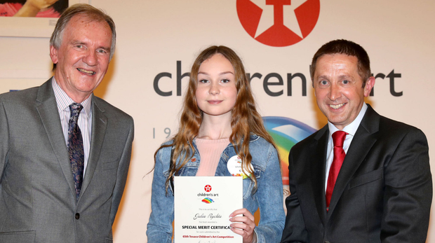Julia Rychta (13), student at Coláiste Muire, Ballymote, who won a special merit award in this years 65th Texaco Childrens Art Competition. Presenting her with the award at a ceremony held in Enfield recently, is Chairman of the judging panel, Professor Gary Granville and James Twohig, Director Ireland Operations at Valero