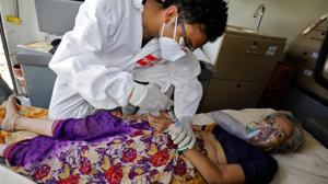 A doctor tends to a patient with a breathing problem inside an ambulance waiting to enter a Covid-19 hospital for treatment in Ahmedabad, India
