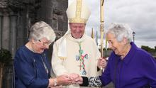 Bishop Dempsey greeting his aunts Margaret Butterly and Kathleen Lenehan as they admire his episcopal ring after the ceremony
