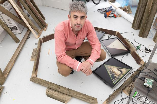 A photograph of artist shane finan in his studio, surrounded by timber, tools and electronics