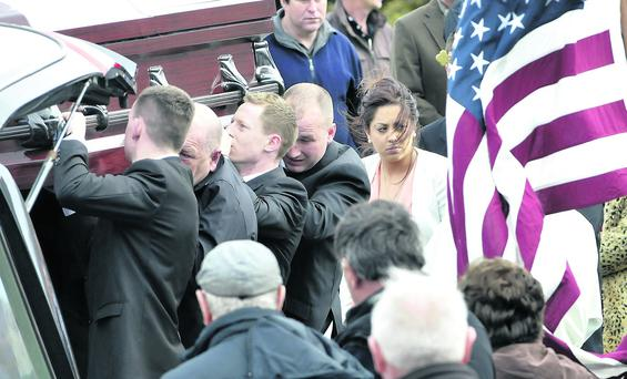 The wife of the late Gary Feeney, Kelly Melvin (in white) walks behind Gary's coffin last Saturday.