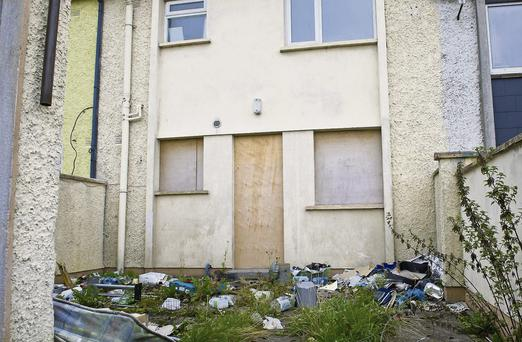 ONE of the houses boarded up at Mountain View with litter in the back garden.