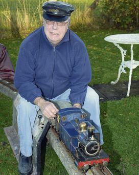 Geoff King aboard his Caledonian Rob Roy model locomotive and trolly at his home.