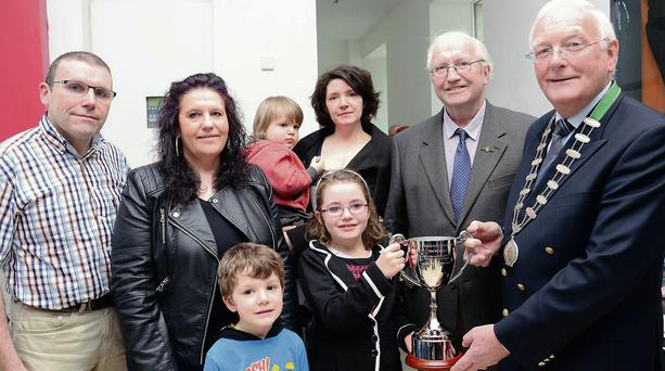 Ceola McGauran presents a Perpetual Cup to Michael Currid President of Feis Shligigh on behalf of the McGauran family in memory of the late Josie McGauran, a long-serving member of the Feis Committee. Pictured from lt. to rt. Briain, Bernardine, Dualta, Catherine, Brian Snr. Front- Briain and Ceola.
