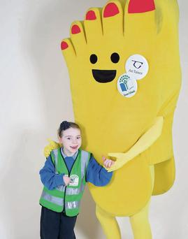 Riverstown schoolgirl Cara Tighe with Green Schools mascot 'Fionn the Foot'.