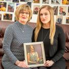 Terri Golden and her daughter Aisling, holding a picture of Grainne at their home