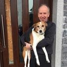 Parish Priest of St Anne's Fr Pat Lombard with parish dog Penny outside one of the damaged doors at St Anne's