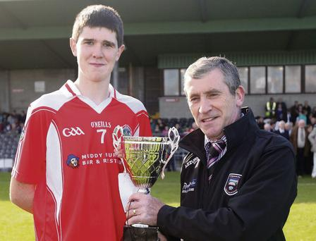 Ciaran Kilcullen, captain, Castleconnor, receives the Minor A2 trophy from Minor Board Chairman, Brendan Leonard.
