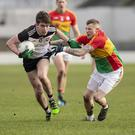 Luke Towey brushes off this tackle from Lee Walker in Netwatch Cullen Park on Sunday. Pic: Thomas Nolan Photography