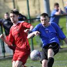 Justin Curron, Cartron United in action with Adam Lynch of Merville United